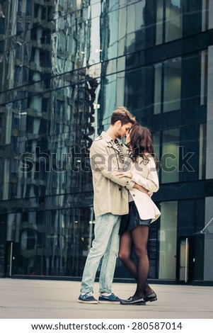 Young fashion couple walking down the street in summer near skyscraper. Pretty beautiful woman in stripes  clothes. Vertical - stock photo
