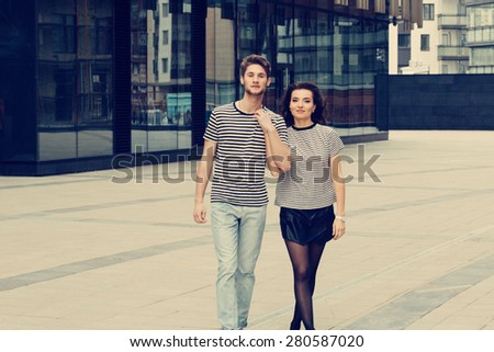 Young fashion couple walking down the street in summer near skyscraper. Pretty beautiful woman in stripes  clothes. Looking camera - stock photo