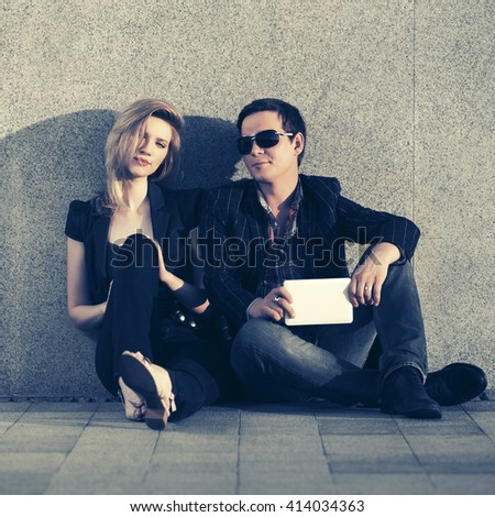 Young fashion couple with tablet computer sitting at the wall. Male and female stylish model. Man and woman outdoor