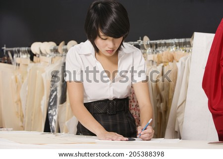 Young fashion designer working at her clothing store - stock photo