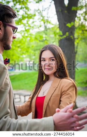 Young fashion elegant stylish couple, in love , stand stand hand in hand on park in spring sunny weather - stock photo