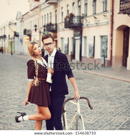 Young fashion elegant stylish couple posing on streets of european city in summer evening weather. Sensual blonde vogue girl with handsome hipster man having fun outdoor. - stock photo