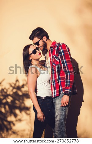 Young fashion elegant stylish couple posing on streets of european city. Sensual brunette vogue girl with handsome hipster man posing near the wall. - stock photo