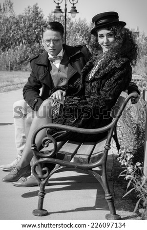 Young fashion elegant stylish retro couple sitting on bench in old vintage town