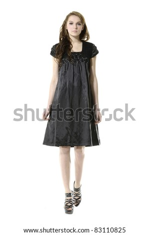 young fashion female in a black dress walking isolated over white - stock photo