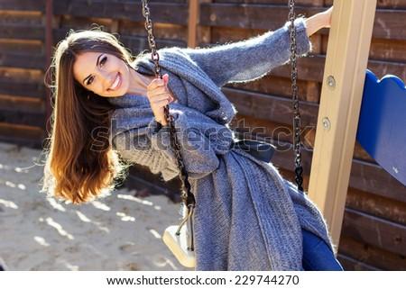 Young fashion girl having fun on swing - stock photo