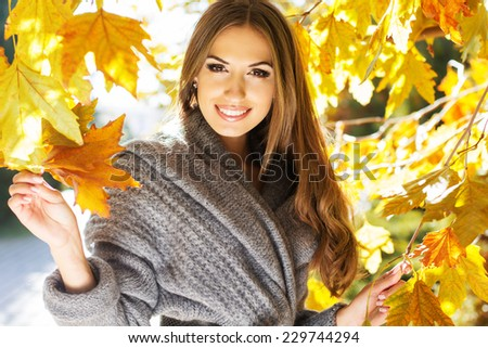 Young fashion girl in autumn park - stock photo