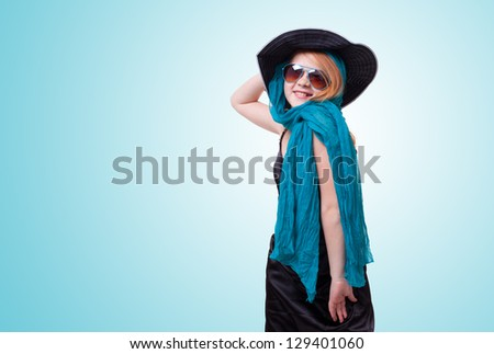 young fashion  girl  in black dress with hat and sunglasses on blue background - stock photo