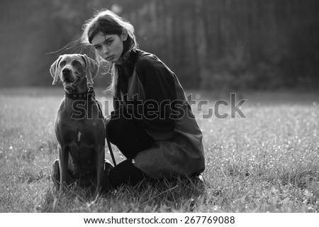 young fashion girl model walk with her dog outdoor park nature background - stock photo