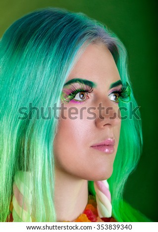 Young fashion glamor girl with colored hair earrings marshmallow, candy makeup . Bright style. candy shop - stock photo