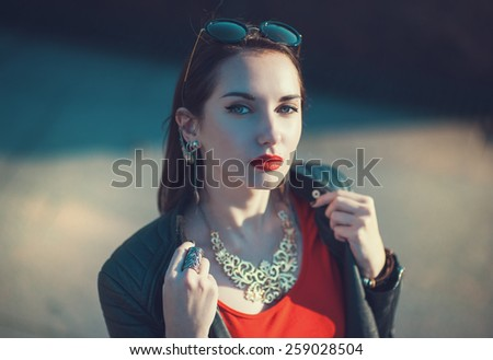 Young fashion hipster beautiful girl in leather jacket and sunglasses outdoor in the city - stock photo