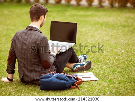 young fashion male student sitting on grass in park and holding a laptop - stock photo