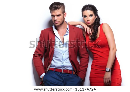 young fashion man and woman against white wall, posing for the camera - stock photo
