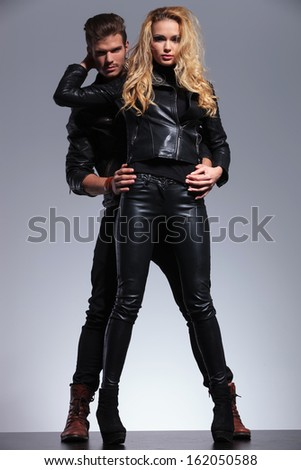 young fashion man embracing his girlfriend from her hack and both looking at the camera - stock photo