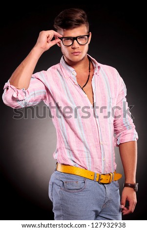 young fashion man holding his glasses while looking at the camera on a black background - stock photo