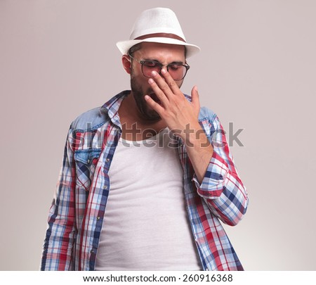 Young fashion man holding his hand to his mouth while yawning. - stock photo