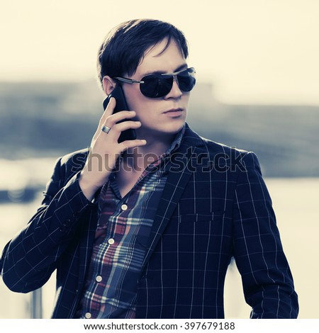 Young fashion man in sunglasses calling on mobile phone outdoor - stock photo