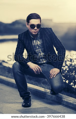 Young fashion man in sunglasses outdoor at sunset