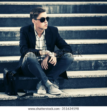 Young fashion man in sunglasses sitting on the steps - stock photo