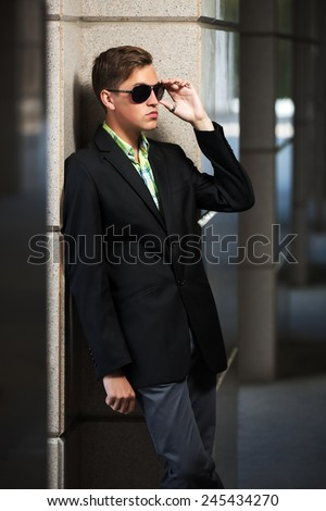 Young fashion man in sunglasses standing at the wall - stock photo