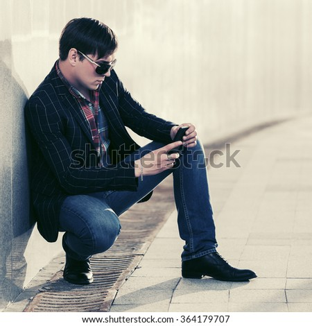 Young fashion man in sunglasses with a mobile phone at the wall