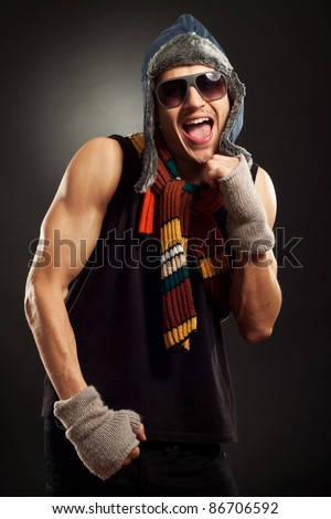 young fashion man in winter clothes and sunglasses in a fight position - stock photo