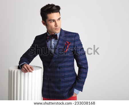 Young fashion man looking away from the camera while holding one arm on a white column. - stock photo
