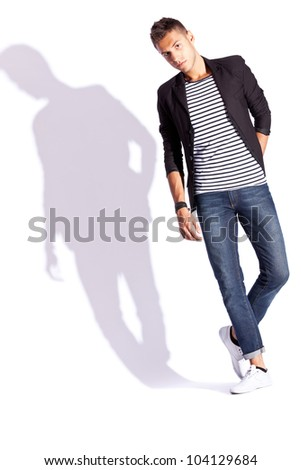 young fashion man looking down and standing with his hands in pockets on white background with hard shadow - stock photo