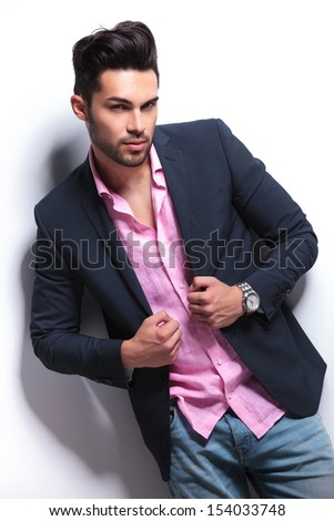 young fashion man posing with his hands on his suit jacket while looking into the camera. on a white background - stock photo