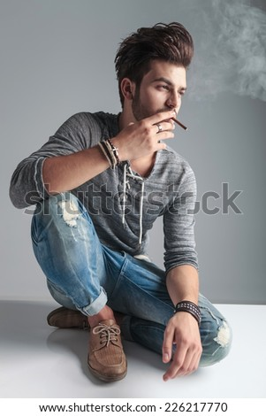 Young fashion man relaxing on the floor while smoking a cigarette, looking away from the camera. - stock photo