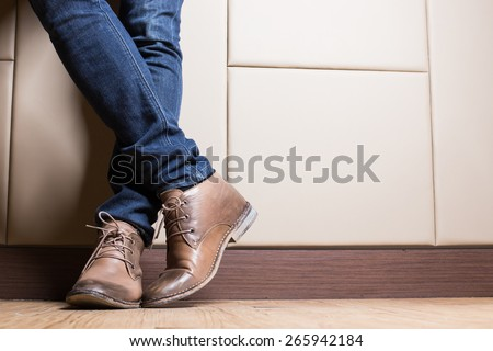 Young fashion man's legs in blue jeans and brown boots on wooden floor - stock photo