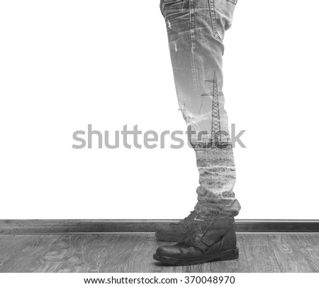 Young fashion man's legs in jeans and boots with power lines pylons double exposure black and white - stock photo