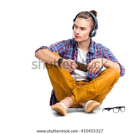 Young fashion man sitting on the floor and enjoying music with his headphones. Handsome young stylish hipster guy in headphones holding smart phone and listening music, isolated on a white background
