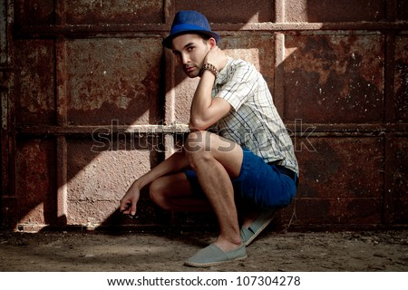 young fashion man squat against old rusty wall - stock photo