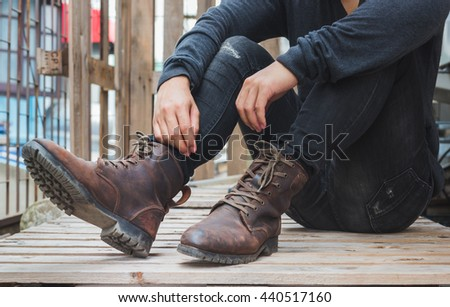 Young fashion man wearing in a black shirt, black jeans and brown leather boots on wooden floor. Old leather boots. - stock photo