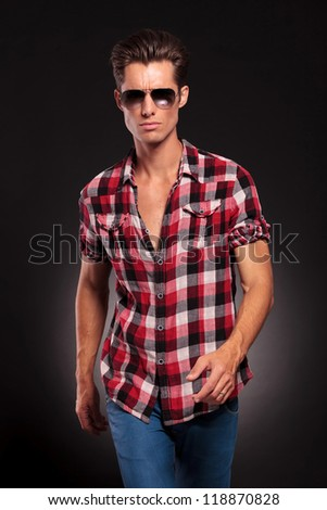 young fashion man wearing sunglasses walking forward on black background - stock photo