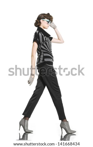 young fashion model in gloves with sunglasses walking in studio