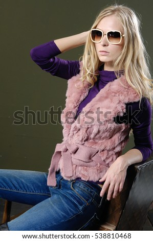 young fashion model in jeans with sunglasses sitting on cube