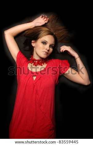 Young Fashion model laying on black background
