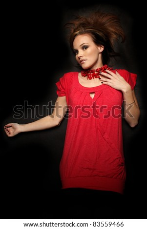 Young Fashion model laying on black background - stock photo