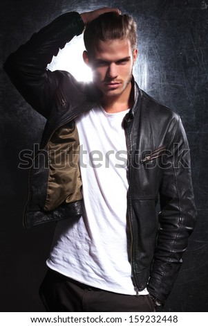 young fashion model moving his hand through his long hair and looking at the camera