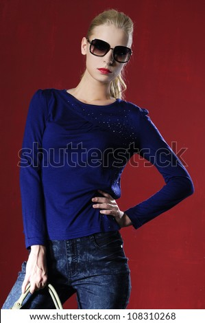 young fashion model posing on red background
