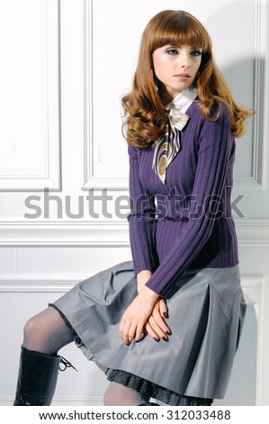 young fashion model sitting cube posing in studio - stock photo