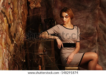 young fashion model sitting on a stool in drama decoration