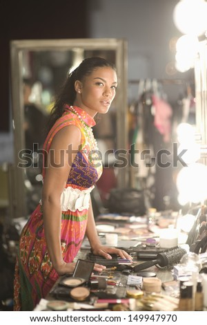 Young fashion model standing with cosmetics at dressing room - stock photo