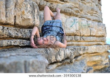 young fashion model wearing blue dress and lying on the rocks