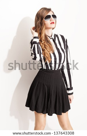 young fashion model with sunglasses and pleated skirt posing on white background - stock photo