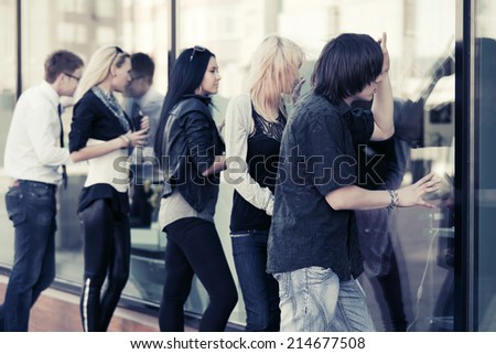 Young fashion people looking through the mall windows - stock photo