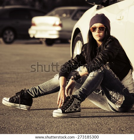 Young fashion punk woman sitting next to her car - stock photo