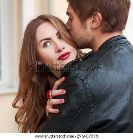 Young fashion sensual couple posing outdoor in cold weather boyfriend gives kiss to his girlfriend